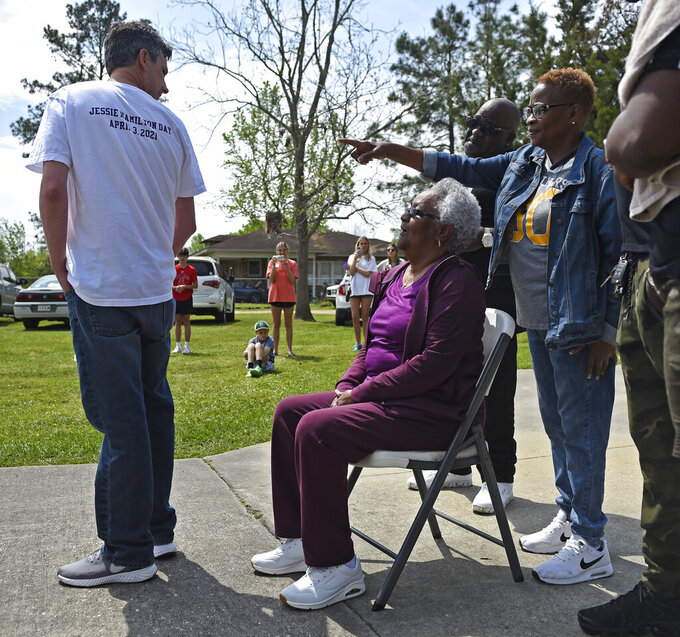 """Andrew Fusaiotti, left, turns around to show Jessie Hamilton, seated, the back of his shirt as Hamilton's daughter, Yonetta Tircuit, right, points as LSU FIJI graduates gather to surprise their former house kitchen staff member, Saturday, April 3, 2021, to pay off her mortgage and celebrate """"Jessie Hamilton Day"""" in Baker, La. (Hilary Scheinuk/The Advocate via AP)"""