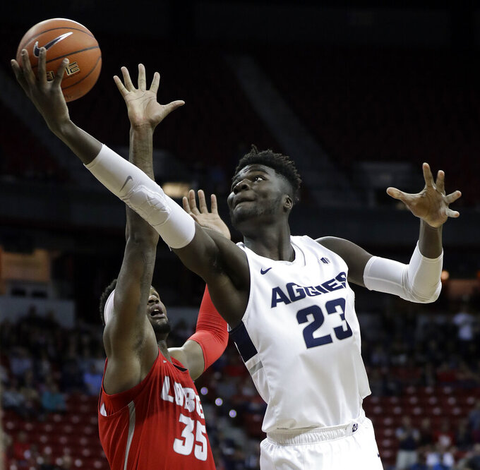 Utah State's Neemias Queta shoots as New Mexico's Carlton Bragg defends during the first half of an NCAA college basketball game in the Mountain West Conference men's tournament Thursday, March 14, 2019, in Las Vegas. (AP Photo/Isaac Brekken)