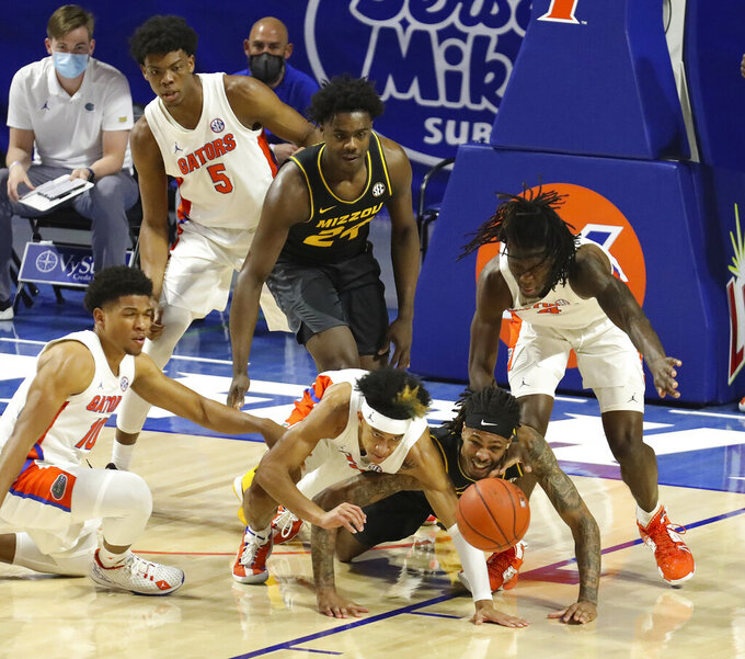Florida guard Tre Mann (1) and Missouri forward Mitchell Smith (5)  go after a loose ball during an NCAA college basketball game, Wednesday, March 3, 2021 in Gainesville, Fla. (Brad McClenny/The Gainesville Sun via AP)