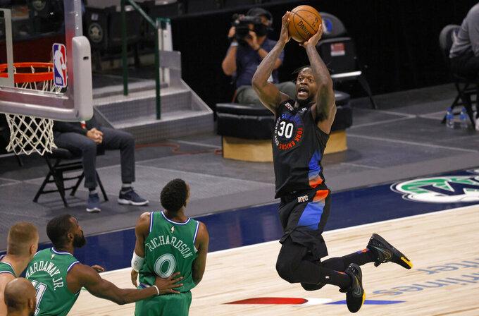 New York Knicks forward Julius Randle (30) drives inside to score as Dallas Mavericks guard Josh Richardson (0) and forward Tim Hardaway Jr. (11) watch during the second half of an NBA basketball game Friday, April 16, 2021, in Dallas. (AP Photo/Ron Jenkins)