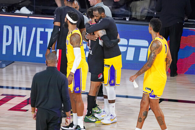 Los Angeles Lakers' LeBron James, second from right, hugs Portland Trail Blazers' Gary Trent Jr. (2) after an NBA basketball first round playoff game Saturday, Aug. 29, 2020, in Lake Buena Vista, Fla. The Lakers won 131-122 to win the series 4-1. (AP Photo/Ashley Landis)