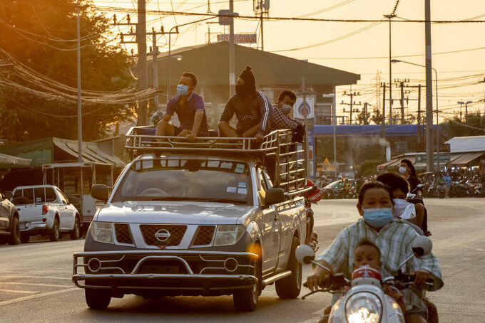 Migrant workers travel in atop of a trucks in Samut Sakhon, South of Bangkok, Thailand, Monday, Jan. 4, 2021. For much of 2020, Thailand had the coronavirus under control. After a strict nationwide lockdown in April and May, the number of new local infections dropped to zero, where they remained for the next six months. However, a new outbreak discovered in mid-December threatens to put Thailand back where it was in the toughest days of early 2020. (AP Photo/Gemunu Amarasinghe)