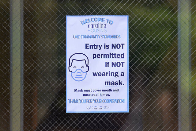 A sign is posted at the entrance to Hinton James dormitory at the University of North Carolina in Chapel Hill, N.C., Tuesday, Aug. 18, 2020. The university announced that it would cancel all in-person undergraduate learning starting on Wednesday following a cluster of COVID-19 cases on campus. (AP Photo/Gerry Broome)