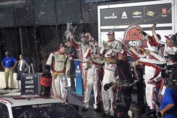 Ryan Blaney, left, is sprayed by crew members while celebrating in Victory Lane after winning a NASCAR Cup Series auto race at Daytona International Speedway, Saturday, Aug. 28, 2021, in Daytona Beach, Fla. (AP Photo/Phelan M. Ebenhack)