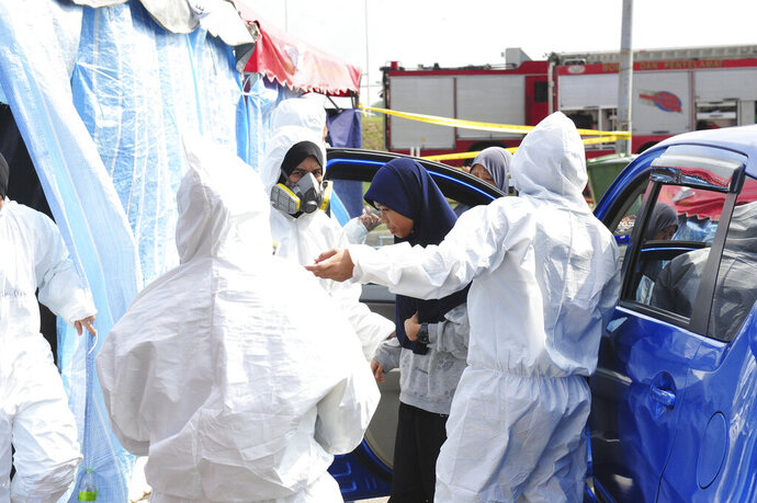 Emergency personnel help a student as she arrives at an evacuation center at Pasir Gudang district in Johor state, Malaysia, Tuesday, June 25, 2019. Malaysia's government has shut more than 100 schools in a southern state after chemical pollution sickened dozens of students for the second time in three months. (AP Photo/Thomas Yong)