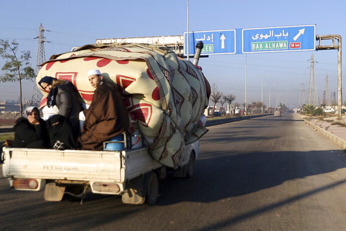 In this frame grab from video taken on Thursday, Dec. 19, 2019, a family with their goods loaded on a lorry drives towards the Turkish border in Syria's rebel-controlled Idlib province. The UN says that some 60,000 Idlib residents have been displaced in recent weeks by a government offensive aimed at dislodging the rebels from their last stronghold in the country.(AP Photo/APTN)