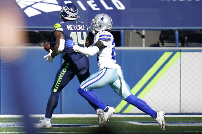 Seattle Seahawks wide receiver DK Metcalf, left, has the ball knocked loose by Dallas Cowboys cornerback Trevon Diggs, right, after catching a pass near the end zone during the first half of an NFL football game, Sunday, Sept. 27, 2020, in Seattle. (AP Photo/Elaine Thompson)
