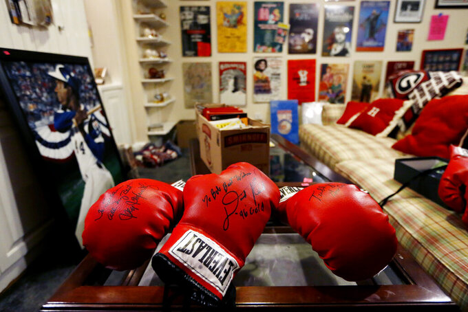 Autographed boxing gloves are seen in Bob Hope's basement, which holds his sports memorabilia collection for sale, Friday, Aug. 23, 2019, in Stone Mountain, Ga. With a name that made him easy to remember, Hope built a behind-the-scenes career as a hype man, a PR wizard who worked for various sports teams around Atlanta before launching his own firm and setting off on a quixotic, around-the-world quest to make friends and move the needle. (AP Photo/Andrea Smith)