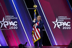 FILE - In this Feb. 29, 2020 file photo, President Donald Trump hugs and kisses the American flag after speaking at Conservative Political Action Conference, CPAC 2020, at the National Harbor, in Oxon Hill. (AP Photo/Jose Luis Magana)