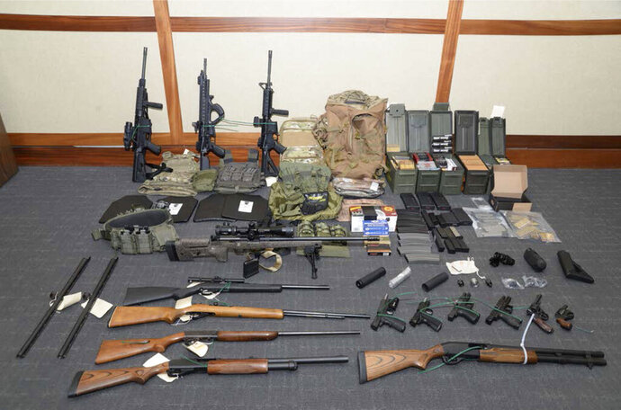 FILE - This undated file photo provided by the Maryland U.S. District Attorney's Office shows firearms and ammunition confiscated from Coast Guard officer Christopher Paul Hasson, accused of stockpiling guns and compiling a hit list of prominent Democrats and network TV journalists. A federal judge on Friday, Sept. 20, 2019, refused to dismiss gun charges against Hasson, accused of being a domestic terrorist who stockpiled weapons and drafted a hit list of prominent Democrats and TV journalists. (Maryland U.S. District Attorney's Office via AP, File)