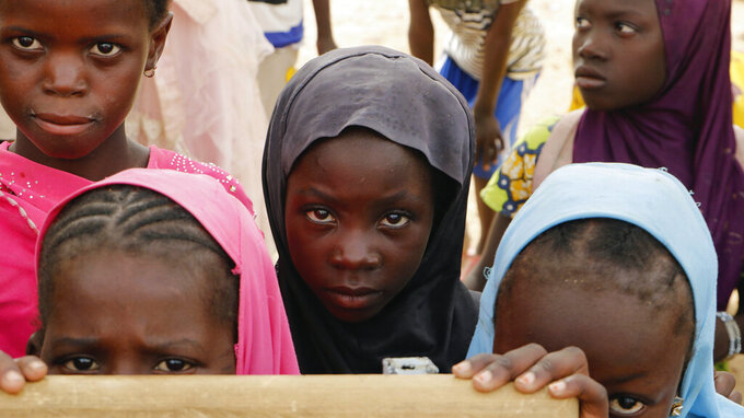 Displaced children attend class in Dori town, Burkina Faso, Saturday Aug. 7, 2021. The Norwegian Refugee Council said Burkina Faso's slow and insufficient humanitarian response to the country's escalating attacks is forcing people to choose between violence or hunger. Surging violence linked to al-Qaida and the Islamic State in the war-weakened West African nation has forced more than 275,000 people from their homes since April _ double those displaced in the previous seven months, according to government statistics. (AP Photo/Sam Mednick)