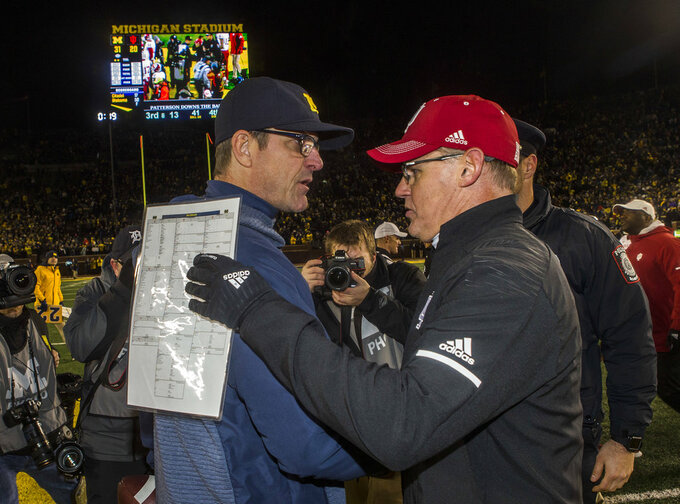 Michigan head coach Jim Harbaugh, left, shakes hands with Indiana head coach Tom Allen after an NCAA college football game in Ann Arbor, Mich., Saturday, Nov. 17, 2018. Michigan won 31-20. (AP Photo/Tony Ding)