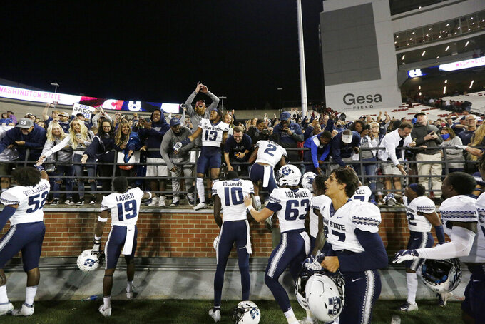 Utah State players celebrate with fans after winning 26-23 against Washington State in an NCAA college football game, Saturday, Sept. 4, 2021, in Pullman, Wash. (AP Photo/Young Kwak)