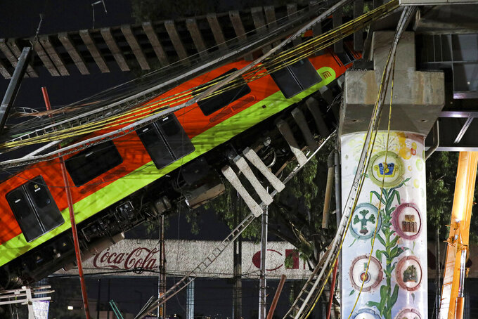 FILE- In this May 4, 2021 file photo, Mexico City's subway cars lay at an angle after a section of Line 12 of the subway collapsed in Mexico City. Poorly welded, badly located and completely missing studs that joined steel support beams to a concrete layer supporting the track bed were to blame for the May 3 collapse that killed 26 people, experts concluded in a report released Tuesday, Sept. 7, 2021. (AP Photo/Marco Ugarte, File)