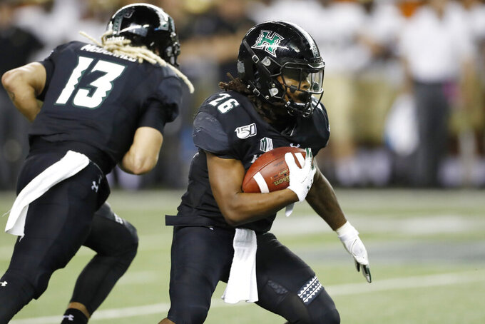 Hawaii running back Miles Reed (26) runs through the Army defense during the second half of an NCAA college football game Saturday, Nov. 30, 2019 in Honolulu. (AP Photo/Marco Garcia)