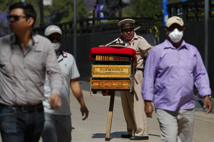 Organ grinder Moises Rosas solicits tips from pedestrians in central Mexico City, Tuesday, March 24, 2020. Rosas, who has been an organ grinder for 25 years, says he isn't afraid of the new coronavirus and needs the average of 200 pesos (around $8.50) he takes home per day.