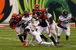 Cincinnati Bengals running back Joe Mixon (28) is tackled by Jacksonville Jaguars cornerback Chris Claybrooks (27) in the first half of an NFL football game in Cincinnati, Sunday, Oct. 4, 2020. (AP Photo/Bryan Woolston)