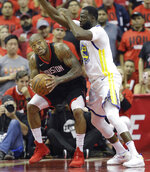 Houston Rockets forward P.J. Tucker, left, is pressured by Golden State Warriors forward Draymond Green (23) during the first half in Game 2 of the NBA basketball Western Conference Finals, Wednesday, May 16, 2018, in Houston. (AP Photo/David J. Phillip)