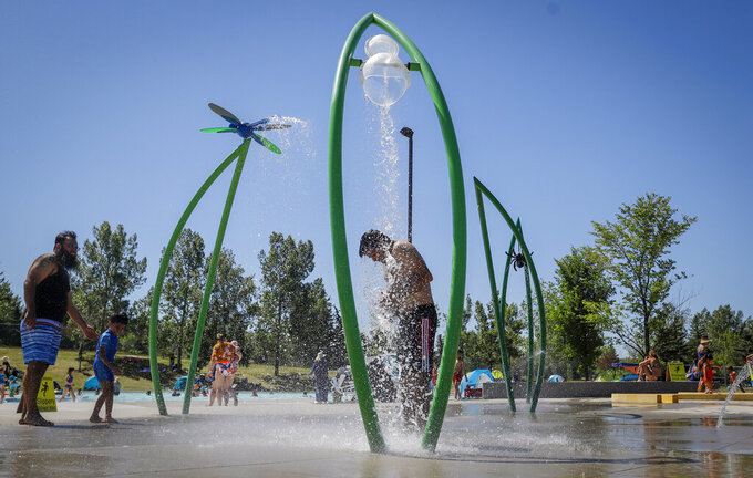 FILE - In this Wednesday, June 30, 2021 file photo, a man stands under a water feature trying to beat the heat at a splash park in Calgary, Alberta. Scientists say there's something different this year from the recent drumbeat of climate weirdness. This summer a lot of the places hit by weather disasters are not used to getting extremes and many of them are wealthier, which is different from the normal climate change victims. That includes unprecedented deadly flooding in Germany and Belgium, 116-degree heat records in Portland, Oregon and similar blistering temperatures in Canada, along with wildfires. Now Southern Europe is seeing scorching temperatures and out-of-control blazes too. And the summer of extremes is only getting started. Peak Atlantic hurricane and wildfire seasons in the United States are knocking at the door. (Jeff McIntosh/The Canadian Press via AP, FIle)