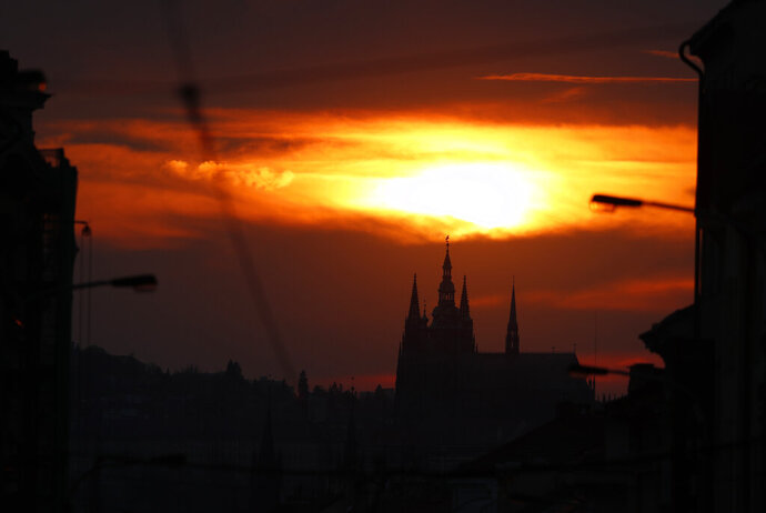 FILE - In this Wednesday, April 10, 2019 file photo, the sun sets behind the St. Vitus cathedral in Prague, Czech Republic. On Tuesday, April 23, 2019, Czech Parliament's lower house has overridden a veto of the upper house to approve a proposal drafted by Communist lawmakers to tax the compensation that the country's churches receive for property seized by the former Communist regime. (AP Photo/Petr David Josek/File)