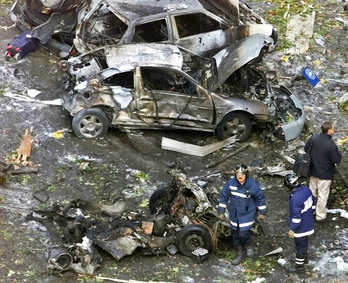 """FILE - In this Nov. 6, 2001 file photo, firefighters work at the scene of a car bomb in Madrid. Josu Urrutikoetxea, the last known chief of ETA, the now-extinct Basque separatist militant group, goes on trial Monday Oct. 19, 2020 in Paris for terrorism charges that he deems """"absurd"""" because of his role in ending a conflict that claimed hundreds of lives and terrorized Spain for half a century. (AP Photo/Paul White, File)"""