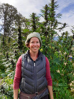 In this undated photo provided by Rosales CBD, Dove Oldham poses in front of a hemp plant growing at Madrona Family Farm in Grants Pass, Oregon. Oldham, who sells hemp-derived CBD products under the name Rosales CBD, says she is concerned about federal rules regulating hemp farming recently published by the U.S. Department of Agriculture. (Rosales CBD via AP)