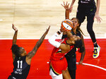 Las Vegas Aces' A'ja Wilson, second from left, looks to shoot under pressure from Seattle Storm's Epiphanny Prince (11) and Mercedes Russell during the second quarter of a WNBA basketball game at Michelob Ultra Arena on Sunday, June 27, 2021, in Las Vegas. (Chase Stevens/Las Vegas Review-Journal via AP)