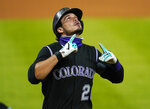 Colorado Rockies' Nolan Arenado points to the sky after hitting a solo home run against the San Francisco Giants during the seventh inning of a baseball game, Wednesday, Aug. 5, 2020, in Denver. (AP Photo/Jack Dempsey)