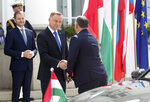 Poland's President Andrzej Duda, center, are welcomes Hungary Prime Minister Viktor Orban, right, for a Visegrad Group summit in Warsaw, Poland, on Friday, July 3, 2020, as Poland takes the rotating presidency of the regional cooperation group that also includes the Czech Republic and Hungary.(AP Photo/Czarek Sokolowski)