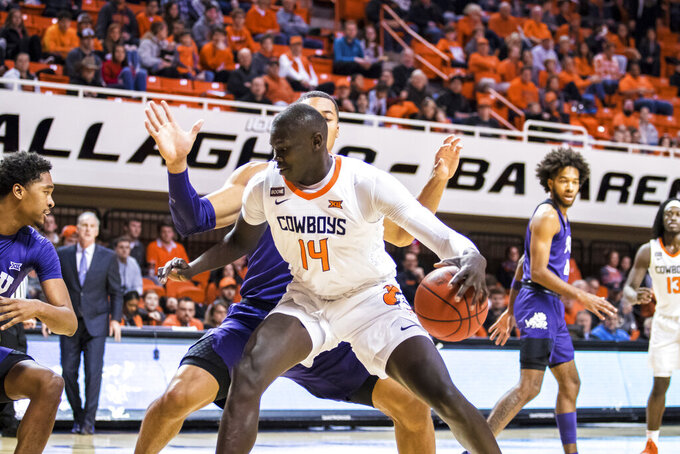 Oklahoma State's Yor Anei works against a TCU defender during an NCAA college basketball game Wednesday, Feb. 5, 2020, in Stillwater, Okla. (Devin Lawrence/Tulsa World via AP)