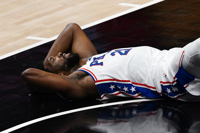 Philadelphia 76ers center Joel Embiid (21) lies on the floor after being called for a foul during the first half of Game 6 of an NBA basketball Eastern Conference semifinal series against the Atlanta Hawks, Friday, June 18, 2021, in Atlanta. (AP Photo/John Bazemore)