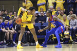 West Virginia forward Gabe Osabuohien (3) looks to pass the ball as Kansas guard Marcus Garrett (0) defends during the first half of an NCAA college basketball game Wednesday, Feb. 12, 2020, in Morgantown, W.Va. (AP Photo/Kathleen Batten)