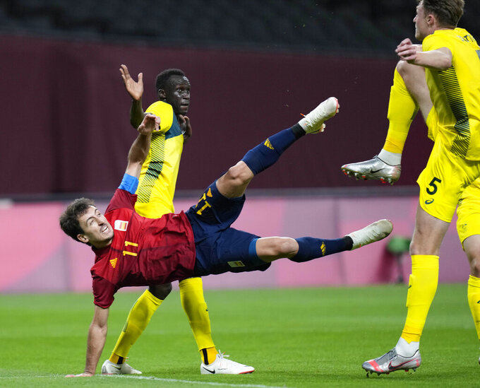 Spain's Mikel Oyarzabal (11) strikes the ball as Australia's Harry Souttar, right, tries to stop him during a men's soccer match at the 2020 Summer Olympics, Sunday, July 25, 2021, in Sapporo, Sapporo, Japan. (AP Photo/Silvia Izquierdo)