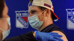 This photo provided by the New York Rangers shows New York Rangers NHL hockey defenseman Jacob Trouba receiving a dose of COVID-19 vaccine at Madison Square Garden in New York on Wednesday, April 7, 2021. The New York Rangers canceled practice so players, coaches and staff could get vaccinated against COVID-19, and Trouba was front and center to take his shot off the ice. (Nick Homler/New York Rangers via AP)