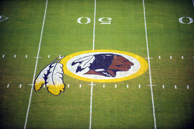 """FILE - In this Aug. 28, 2009 file photo, the Washington Redskins logo is shown on the field before the start of a preseason NFL football game against the New England Patriots in Landover, Md.  The Washington NFL franchise announced Monday that it will drop the """"Redskins"""" name and Indian head logo immediately, bowing to decades of criticism that they are offensive to Native Americans.  (AP Photo/Nick Wass, File)"""