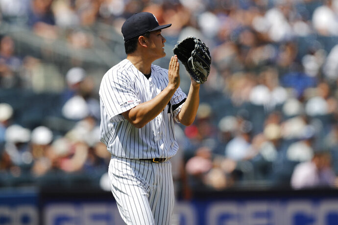 New York Yankees starting pitcher Masahiro Tanaka applauds his third baseman after a play during the sixth inning in a baseball game against the Toronto Blue Jays, Sunday, July 14, 2019, in New York. (AP Photo/Kathy Willens)