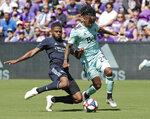 Orlando City's Ruan, left, tries to get the ball away from Vancouver Whitecaps' Yordi Reyna (29) during the first half of an MLS soccer match, Saturday, April 20, 2019, in Orlando, Fla. (AP Photo/John Raoux)