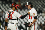 Baltimore Orioles catcher Pedro Severino, left, talks with pitcher Mike Baumann as he enters the game in relief during the fifth inning of a baseball game against the Kansas City Royals, Tuesday, Sept. 7, 2021, in Baltimore. (AP Photo/Julio Cortez)