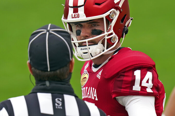 "Indiana quarterback Jack Tuttle (14) talks to an official before the Outback Bowl NCAA college football game against Mississippi Saturday, Jan. 2, 2021, in Tampa, Fla. Indiana covered the Outback Bowl patch to cover the Big Ten logo on their uniforms and added LEO, which stands for ""Love Each Other"" to their helmets. (AP Photo/Chris O'Meara)"