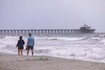 Walkers stroll past Cherry Grove pier at dawn in North Myrtle Beach. Tropical Storm Isais is moving up the east coast and is expected to make landfall near Myrtle Beach, S.C., on Monday, Aug. 3, 2020. (Jason Lee/The Sun News via AP)