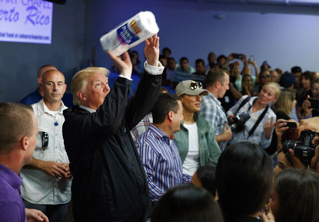 FILE - In this Oct. 3, 2017, file photo, President Donald Trump tosses paper towels into a crowd at Calvary Chapel in Guaynabo, Puerto Rico, after Hurricane Maria devastated the region. Ahead of Vice President Mike Pence's Latinos for Trump rally in central Florida, state Democrats have paid for a billboard showing an image of the president tossing paper towels, seen like this photo, at a Puerto Rican church after the island was devastated by Hurricane Maria. (AP Photo/Evan Vucci, File)