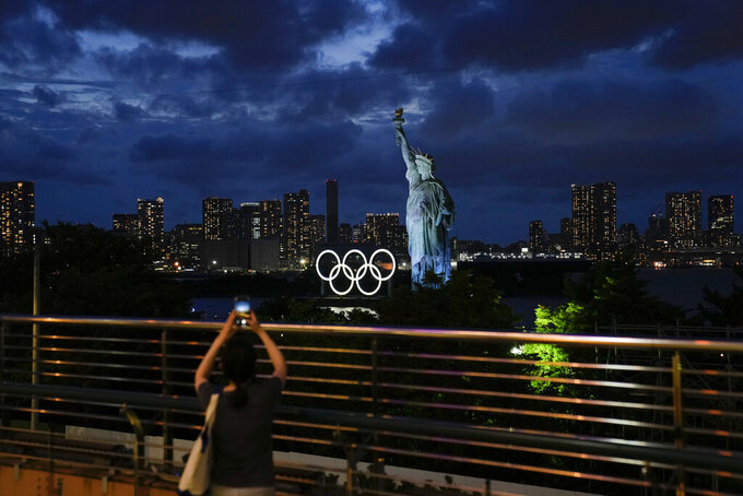 A woman takes pictures of the Olympic rings mounted on a barge floating in the water near a replica of the Statue of Liberty during the 2020 Summer Olympics, Thursday, July 29, 2021, in Tokyo, Japan. (AP Photo/Jae C. Hong)