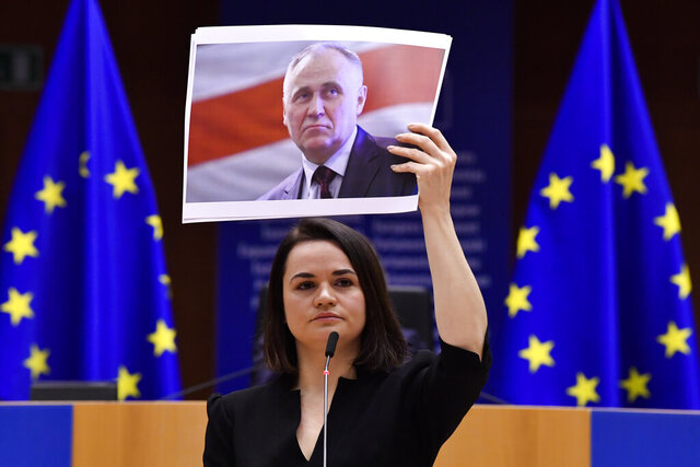 Belarusian opposition politician Sviatlana Tsikhanouskaya holds a picture of Belarusian politician Mikalai Statkevich as she gives a speech during the Sakharov Prize ceremony at the European Parliament in Brussels, Wednesday, Dec. 16, 2020. The European Union has awarded its top human rights prize to the Belarusian democratic opposition. (John Thys/Pool Photo via AP)
