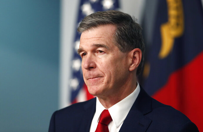 FILE - Gov. Roy Cooper listens to a question during a briefing at the Emergency Operations Center in Raleigh, N.C., Tuesday, July 14, 2020, amid the coronavirus pandemic. Cooper will discuss the pandemic, education and his re-election bid in an interview with The Associated Press on Thursday, Aug. 6. (Ethan Hyman/The News & Observer via AP, File)