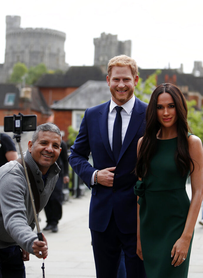 A tourist poses to take a photo of the waxwork figures of Britain's Prince Harry and Meghan Markle against a backdrop of Windsor Castle, in Windsor, England, Wednesday, May 16, 2018. Preparations continue in Windsor ahead of the royal wedding of Britain's Prince Harry and Meghan Markle Saturday May 19. (AP Photo/Alastair Grant)