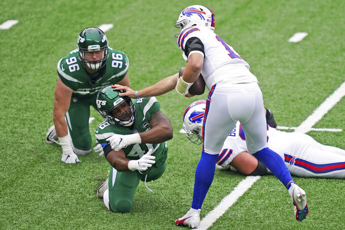 Buffalo Bills quarterback Josh Allen (17), right, holds off New York Jets' Jordan Jenkins during the first half of an NFL football game, Sunday, Oct. 25, 2020, in East Rutherford, N.J. (AP Photo/John Minchillo)