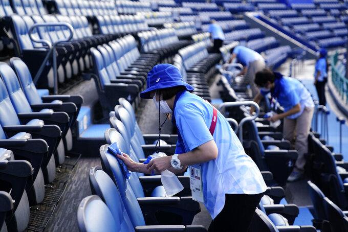 Workers clean seats between softball games at the 2020 Summer Olympics, Saturday, July 24, 2021, in Yokohama, Japan. (AP Photo/Matt Slocum)