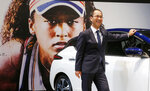 """In this Nov. 1, 2018, photo, Masao Tsutsumi, general manager in charge of Osaka-related marketing at Nissan Motor Co., stands with a Leaf electric vehicle in front of a giant poster of Japanese tennis player Naomi Osaka at the company's showroom in Yokohama, south of Tokyo. Osaka is headed for big money with both Japanese and global appeal. Nissan signed Osaka as its three-year """"brand ambassador"""" in September. Although the deal was in the works for a while, the timing couldn't have been better, coming right after the U.S. Open where she beat Serena Williams of the U.S. (AP Photo/Yuri Kageyama)"""