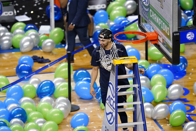 Georgia Tech guard Jose Alvarado holds his portion of the net as he celebrates his team's 80-75 win over Florida State in the Championship game of the Atlantic Coast Conference tournament in Greensboro, N.C., Saturday, March 13, 2021. (AP Photo/Gerry Broome)