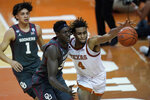 Texas forward Greg Brown (4) and Oklahoma forward Kur Kuath, center, chase the ball during the first half of an NCAA college basketball game Tuesday, Jan. 26, 2021, in Austin, Texas. (AP Photo/Eric Gay)